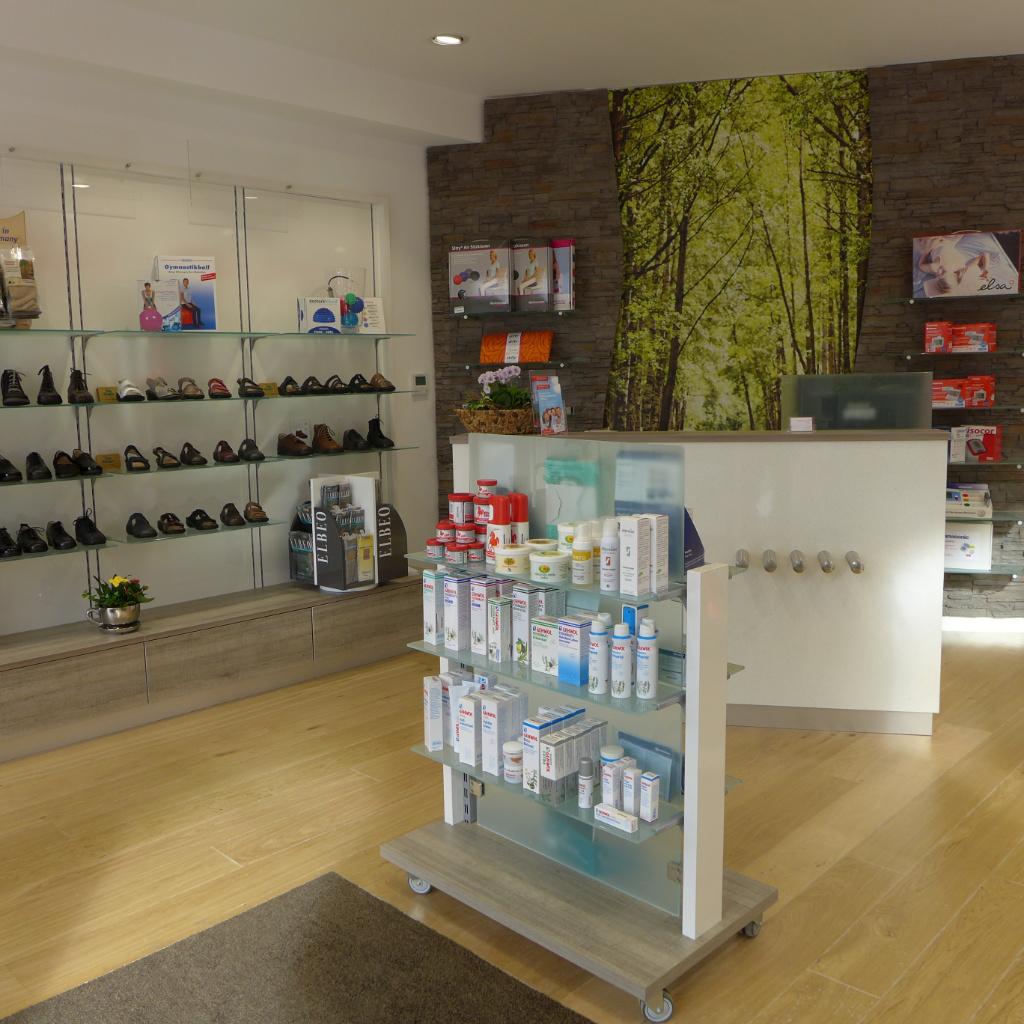Freiwahl mit Glasböden und Schubladen, fahrbare Glasgondel, Verkaufstheke und Sichtwahl mit geschwungener Steinwand mit LED. Firma AT Design Team.