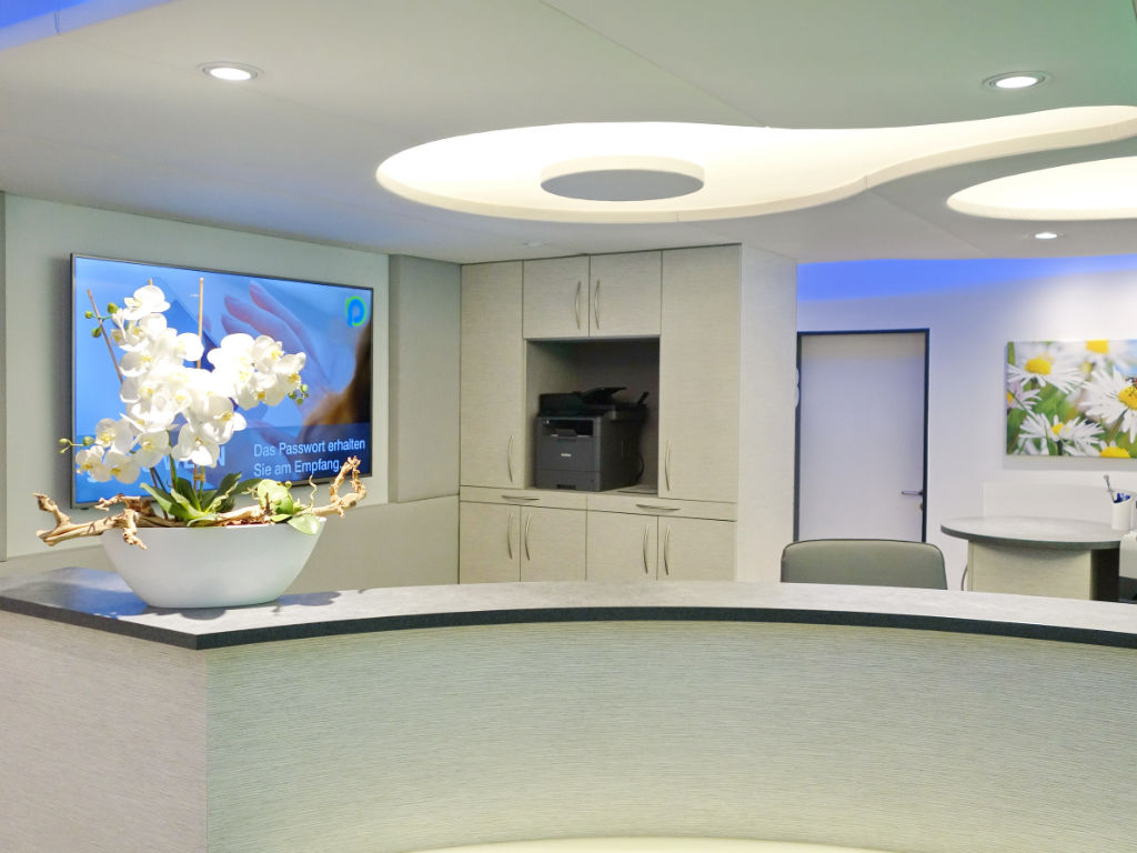 Umbau des Empfangsbereichs der Arztpraxis Dr. Fröhlich. Neue Thekenanlage, Decke, Boden und Wände. Neue Beleuchtung mit LED-Technik.